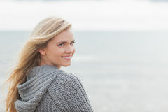 Cute young woman in gray knitted jacket on beach Stock Photos