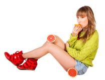 Cute young woman in a green sweater with grapefruits eating Stock Image