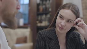 Cute young woman and a handsome bearded blond man sitting at the table. The man telling a story to his girlfriend. The. Glamour brunette woman and a handsome stock video