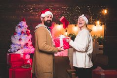 Cute young woman and handsome man with Santa dress. Handsome bearded hipster Santa with smiling positive young woman. Cute young women and handsome men with royalty free stock photo