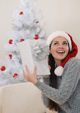 Cute young woman happy to get her present for Christmas Royalty Free Stock Photos