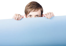 Cute young woman hiding behind promo billboard Royalty Free Stock Photo