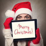 Cute young woman hiding behind tablet computer wearing Santa hat Stock Image