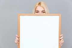 Cute young woman hiding her face behind blank white board. Cute blonde young woman hiding her face behind blank white board over gray background Royalty Free Stock Images