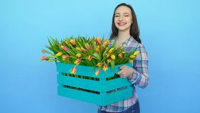 Young woman holding a box of fresh blossoming tulips. Cute Young woman holding a box of fresh blossoming tulips stock video footage