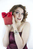 Cute young woman holding glittering, red gift box Royalty Free Stock Photography