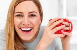 A cute young woman is holding a red cup sitting at a table in a white office. Coffee break. A cute young woman is holding a red cup sitting at a table in a Royalty Free Stock Photo