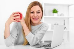 A cute young woman is holding a red cup sitting at a table in a white office. Coffee break. A cute young woman is holding a red cup sitting at a table in a Stock Photography