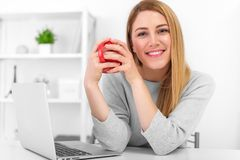 A cute young woman is holding a red cup sitting at a table in a white office. Coffee break. A cute young woman is holding a red cup sitting at a table in a Stock Image