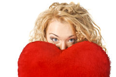 Cute young woman holds a heart symbol to her face Stock Photo