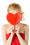 Cute young woman holds a heart symbol to her face Royalty Free Stock Photography