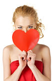 Cute young woman holds a heart symbol to her face Stock Photos