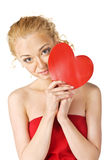 Cute young woman holds a heart symbol to her face Royalty Free Stock Photos