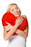Cute young woman holds a heart symbol to her face Stock Photography