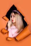 Cute young woman in a hole in a paper Stock Photography