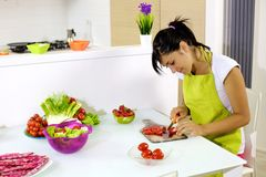 Cute young woman at home preparing salad Stock Images