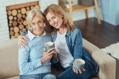 Cute young woman hugging her grannie while holding a cup. Happy relatives. Pleasant young kind women softly hugging her aged cute grandmother while sitting on a Royalty Free Stock Photography