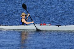 Cute young woman kayaking in California. Cute young woman in straw hat is kayaking in idyllic blue waters of Mission Bay, San Diego, California Royalty Free Stock Photo