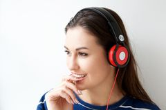 Cute young woman listening to music with headphones. Close up portrait of cute young woman listening to music with headphones Stock Photo