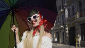 Cute young woman looking at the camera holding multicolored umbrella standing on the street. Attractive fashionable girl. Positive beautiful young woman looking stock footage