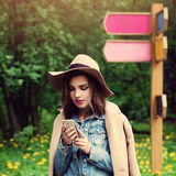 Cute Young Woman Looking at her Mobile Phone Outdoors Royalty Free Stock Image