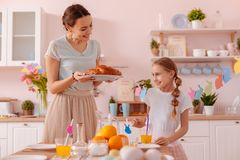 Cute young woman looking at her pretty daughter. Dinner time. Pretty longhaired girl expressing positivity while spending day with her parent royalty free stock images