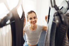 Cute, young woman looking for something to wear Stock Photos