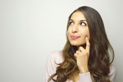 Cute young woman looking to the side the copyspace thinking what to buy on white background.  royalty free stock photo