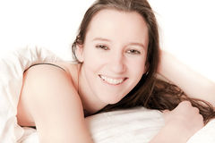 Cute young woman lying in bed Stock Image