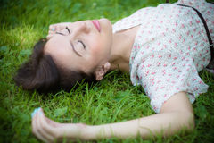 Cute young woman lying on the grass. Stock Photography