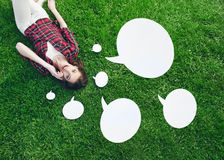 Cute, young woman lying on the grass, talking on the cell phone with speech bubbles Royalty Free Stock Photos