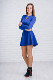 Cute young woman in navy blue dress on white background Stock Photo