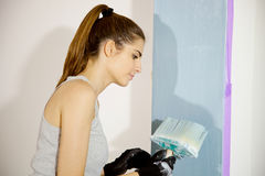 Cute young woman painting renovating home blue color Stock Photo