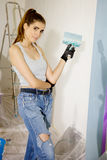 Cute young woman painting renovating home Stock Image