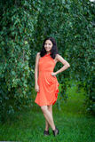 Cute young woman in a park. Picture of beautiful elegant young woman in coral dress standing in summer park stock photo