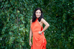 Cute young woman in a park. Picture of beautiful elegant young woman in coral dress standing in summer park stock photos