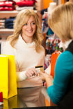 Cute young woman paying after succesfull purchase  Royalty Free Stock Images