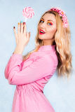 Cute young woman in a pink dress holding a candy Stock Image
