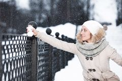 Cute young woman playing with snow in fur coat outdoors Royalty Free Stock Image