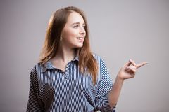 Cute young woman points a finger away on a light gray background with copy space or text, advertising, image. Attractive redhead stock photo
