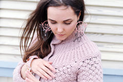 Cute young woman portrait dressed in gentle sweater and handmade boho style earrings Stock Photo
