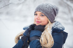 Cute young woman portrait playing with snow in warm woolen hat and coat in winter park Royalty Free Stock Image