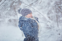 Cute young woman portrait playing with snow in warm woolen hat and coat in winter park Stock Photo