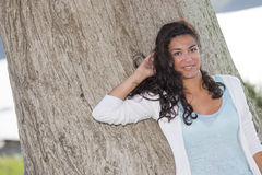 Cute young woman posing in front of large tree trunk. Pretty young woman (20s) enjoying and looking at camera in nature. Large trunk tree on background. Head and Stock Photo