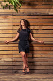 Cute young woman posing on wood fence background Royalty Free Stock Photography