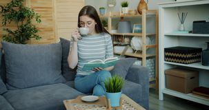Cute young woman reading book and drinking tea indoors in cozy house. Cute young woman is reading interesting book and drinking tea indoors in cozy house stock video