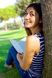 Cute young woman reading book in park in the summer Stock Photo