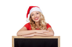 Cute young woman in santa claus hat hiding face behind blank white board Stock Images