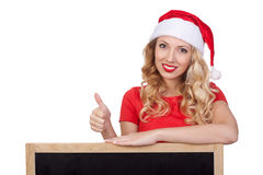 Cute young woman in santa claus hat hiding face behind blank white board Royalty Free Stock Photography