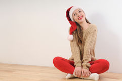 Cute young woman in santa hat dreaming of Christmas gift Stock Image